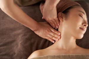 フェイシャルエステで肩と首リンパのマッサージの施術を受けている女性