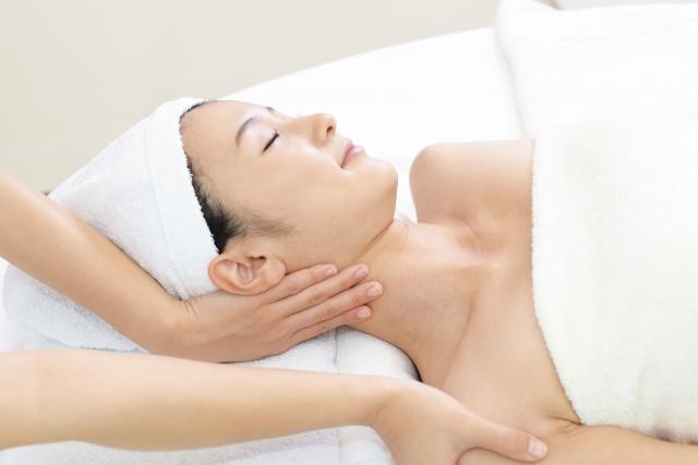 フェイシャルエステで首筋のマッサージを受けている50代の女性
